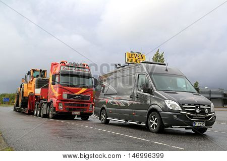 FORSSA, FINLAND - SEPTEMBER 4, 2016: Mercedes-Benz Sprinter pilot vehicle and Volvo FH semi truck transporting wheel loader as oversize load parked on a truck stop asphalt yard on a rainy day.
