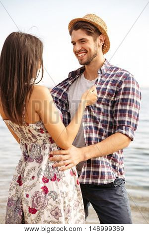 Close up portrait of a happy young hipster couple in love standing at the beach and hugging