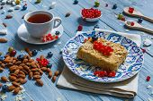 Sweet breakfast with pastry pie and berries - cowberry, red currant and bluberries. Beautiful food served at blue rustic wooden table, cake dessert at ethnic porcelain plate, almonds and tea cup. poster
