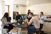 Students Relaxing In Kitchen Of Shared Accommodation poster