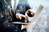 Closeup of two businessmen's hands using laptop on city background. Double exposure poster