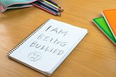 An Horizontal image / poster covering the Social Issues of child abuse a note left on a desk by a child asking for help by a written message saying I am being bullied with a sad face . Room for copy space and text poster
