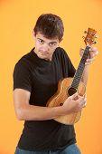 Serious Latino teen ukulele player on an orange background poster