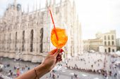 Holding a glass of spritz aperol drink on the main square with Duomo cathedral on the background in Milan city poster