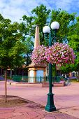 Courtyard in a park including a lamp with hanging flowers taken in Santa Fe, NM poster