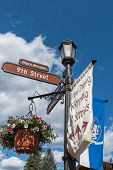 Street sign in bavarian village of Leavenworth, Washington with flower pots and Alpen Strasse poster