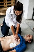 girl making CPR and heart massage to an unconscious man poster