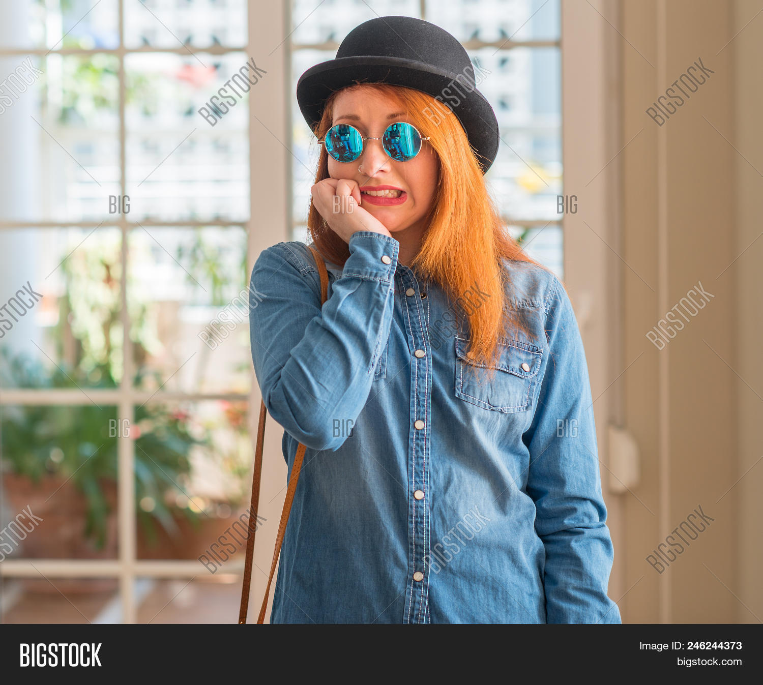Stylish redhead woman wearing bowler hat and sunglasses looking stressed  and nervous with hands on mouth 84277fd6ac59