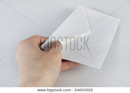 Female Hand Holding An Envelope Over White Background.
