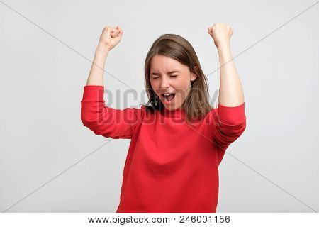 Happy Caucasian Woman In Red Sweater Exults Pumping Fists Celebrates Success Or Victory Of Her Footb