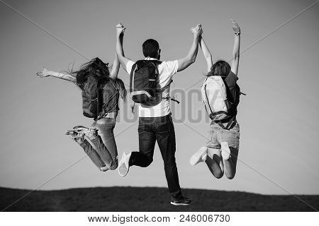 Concept Of Success. Success. Three Friends Or Tourists Jumping On Mountain Top On Blue Sky. Handsome