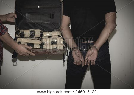 Drug Traffickers Were Arrested Along With Their Heroin. Police Arrest Drug Trafficker With Handcuffs
