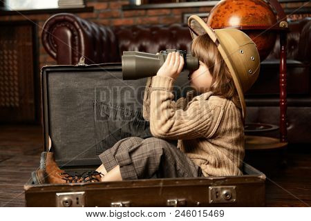 Cute child boy in a travel suitcase playing at home. Childhood. Fantasy, imagination.