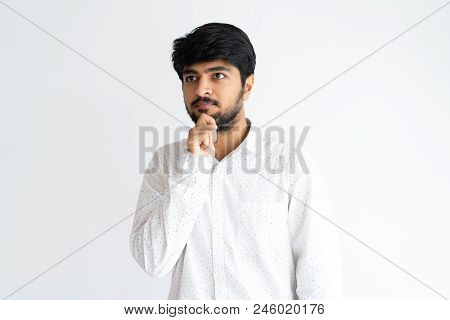 Pensive Young Man Touching Chin And Looking Away. Indian Guy Thinking. Contemplation Concept. Isolat