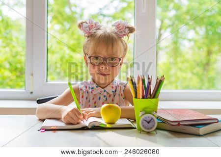 Little Girl With School Supplies Is Sitting At The Table.