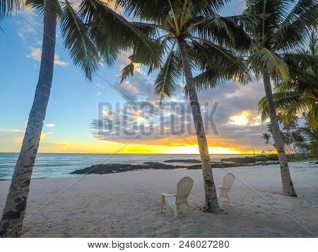 Two Deck Chairs Under Palm Trees At Sunset On An Empty Beach At Lefaga, Matautu, Upolu Island, Weste