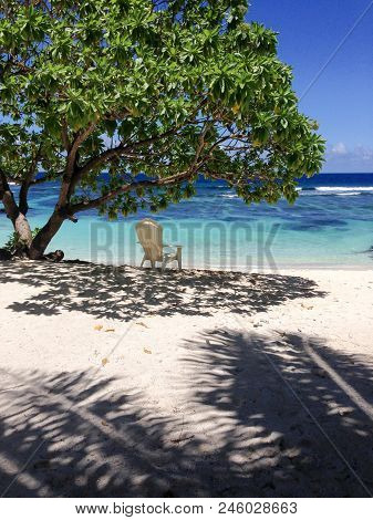 Solitude - A Single Deckchair For Relaxation In The Shade On A Beautiful Tropical Sandy Beach At Lef