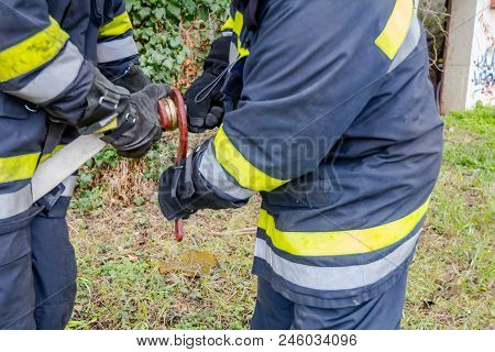 Firefighter Is Helping Fellow To Assembly Water Gun On The Hose Coupler.