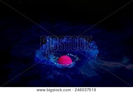 Pink Liquid Is Dropped Into A Surface Tank Of Blue Liquid And Nestles On The Surface. Liquid Drop Ar