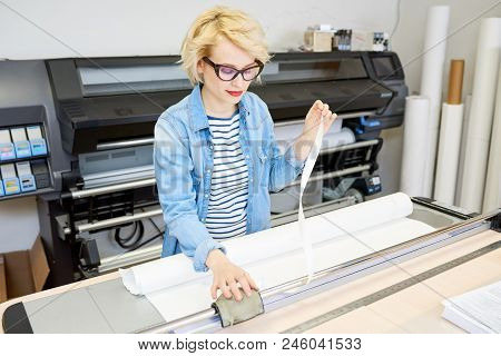 Beautiful Young Woman In Glasses Printing Drafts On Plotter During Work In Office.