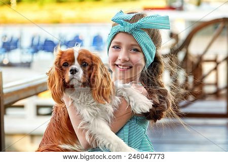 Happy Child With Dog. Portrait Close-up Joy Face Girl Hugs Puppy Breed Cocker Spaniel, Cavalier Char