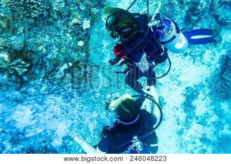 Tourists scuba diving at coral reef under water in tropical ocean