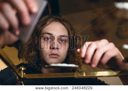 Conceptual close-up portrait of a teenager affected by drug abuse staring while preparing powdered cocaine for snorting at home