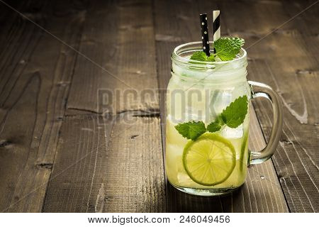 Cold Mojito Cocktail With Ice, Lemon And Mint Leaves In Mason Jar On Rustic Dark Wooden Background A