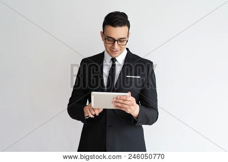 Content Confident Handsome Businessman In Glasses Using Tablet. Positive Successful Young Business E