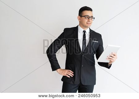 Pensive Handsome Entrepreneur In Glasses Using Tablet And Looking Aside. Content Thoughtful Young Bu