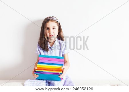 Portrait Of Little Tired Schoolgirl That Leaning On Colorful School Books. Back To School Concept