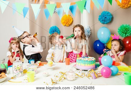 Group Of Smiling Children Playing On The Birthday Party In Decorated Room. Happy Kids Blowing In Pip