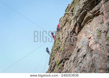 Rock Climbing. A Group Of Young Rock Climbers Climb The Vertical Granite Rock. Extreme Sport