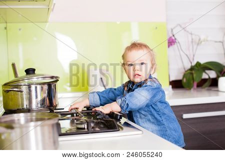 Cute Boy Playing With The Gas Stove By Himself. Small Boy Left Alone In The Kitchen, Playing With Th