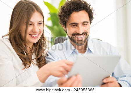 Business people examining data on a digital tablet