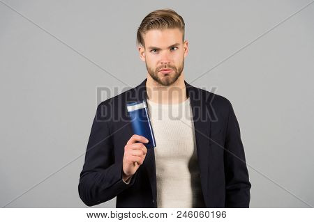 Confident In Hair Care Product. Man Stylish Hairstyle Holds Bottle Hygienic Product Grey Background.