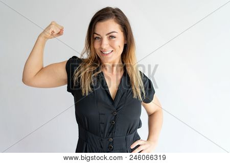 Positive Joyful Lady Showing Hand Muscles. Middle Aged Caucasian Woman In Casual Wear Flexing Bicep.
