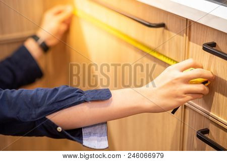Young Asian Man Using Tape Measure For Measuring Wooden Kitchen Counter In Warehouse. Shopping Furni