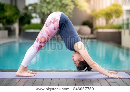 Young Asian Attractive Woman Doing Yoga Exercise With Downward Facing Dog Posing (adho Mukha Svanasa
