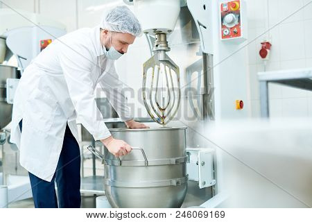 Confectionery Factory Worker In White Coat Operating Dough Mixing Machine.