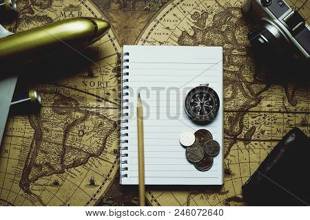 Notebook, camera, pencil, compass, coin, wallet, airplane on blur vintage world map, journey concept, copy space, retro tone poster