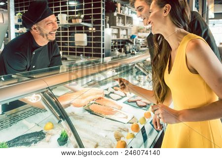 Experienced master chef taking a fresh fish from the freezer to cook it for a female customer and her partner at a trendy restaurant
