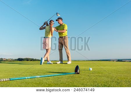 Full length of a skilled golf instructor teaching a young woman to swing the driver club for a professional shot, during class for beginners outdoors on a green field