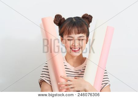 Portrait Of A Pretty Woman In Striped T-shirt Holds Drawings In Rolls Standing Over White Background