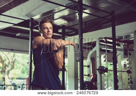 Waist-up Portrait Of Sporty Handsome Man Looking Away While Doing Stretching Exercise For Arms, Inte