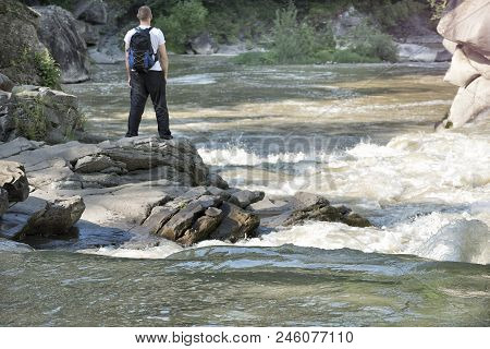 Young Man With A Backpack Is Standing On The Bank Of A Stormy River. Sunny Summer Day