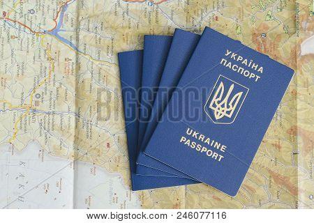 Kharkov, Ukraine- 13 April 2018: Four Blue Ukrainian Passport On A Map. Travel Concept