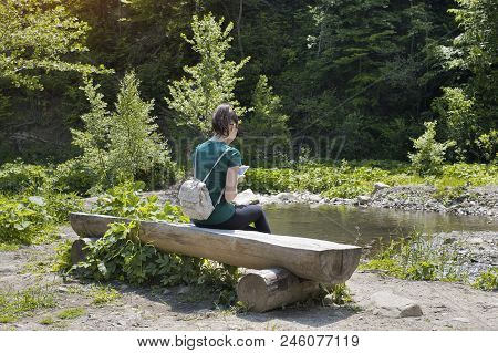 Girl With A Backpack And A Smartphone Sitting On A River Bank. Summer Sunny Day