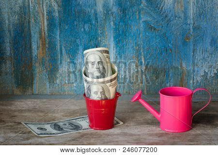 Little Watering Can And Dollars In Pot. Old Wooden Background. Business Concept