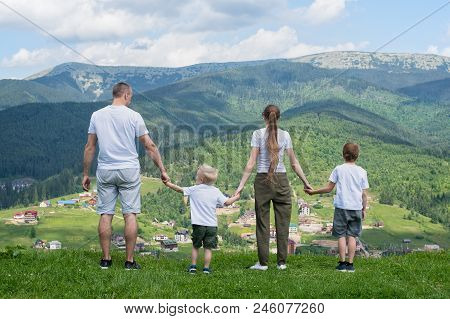 Family Holiday. Parents And Two Sons Admire Views Of The Valley. Mountains In The Distance. Back Vie